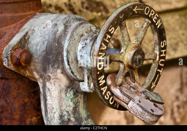 antique water shut off valve secured by a padlock stock image