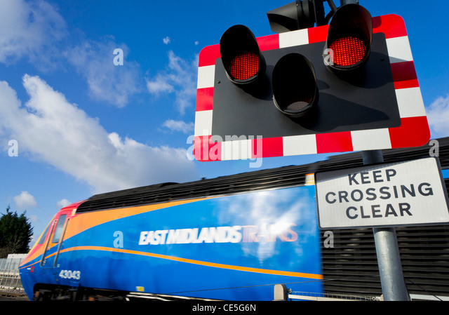 red lighting train. speeding train passing an automated railway level crossing sign red light england gb uk - stock lighting