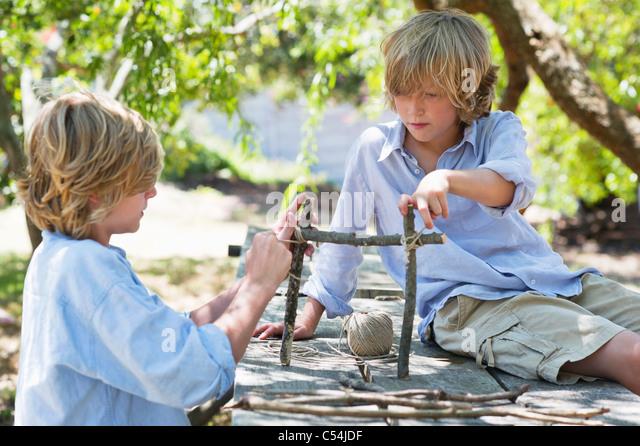 children making frame of driftwood outdoors stock image