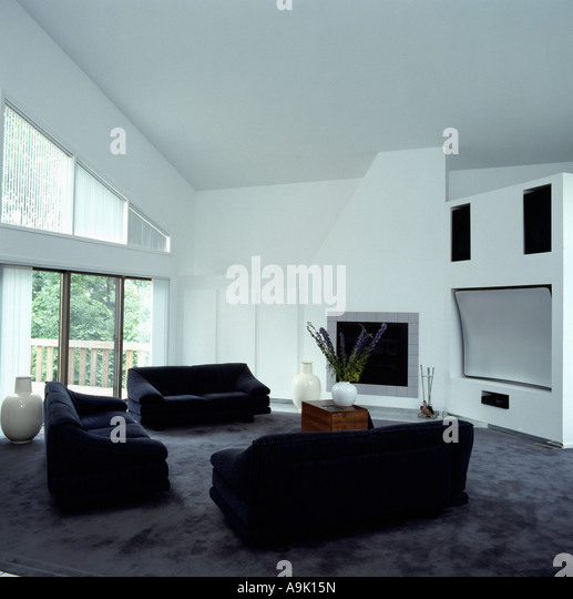 Black Sofas And Grey Carpet In White Eighties American City Livingroom With  Large Television On The