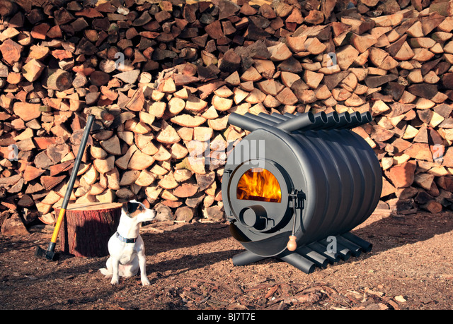 A large wood-burning stove in front of a pile of wood with a small - Wood Burning Stoves Stock Photos & Wood Burning Stoves Stock