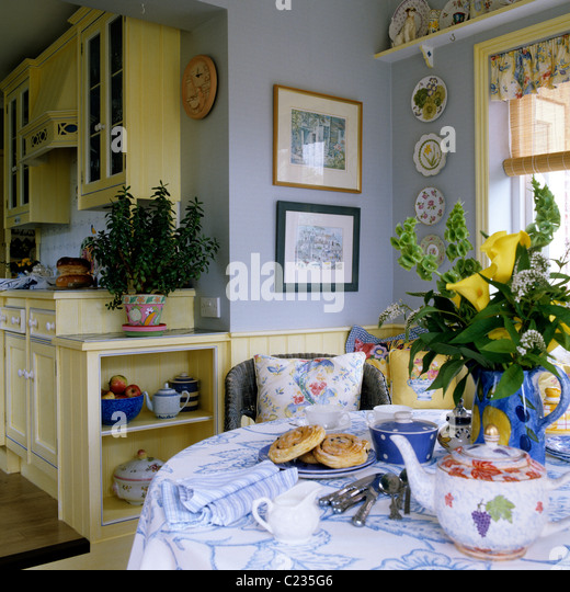 Table Laid With Tea And Pastries In Traditional English Country Kitchen With Yellow Units Stock