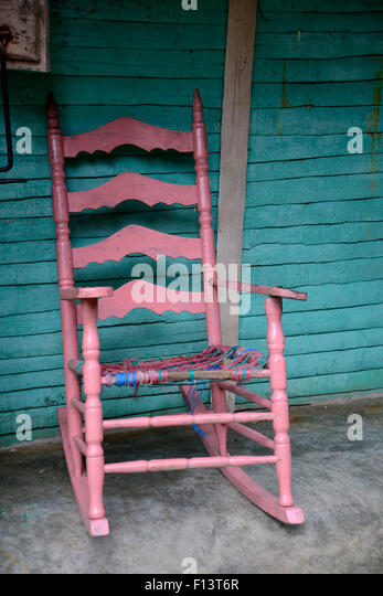 An Old Pink Wooden Rocking Chair Sitting On A Porch   Stock Image