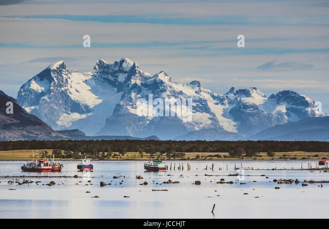 Puerto Natales harbour in front of snowy mountainscape - Stock Image
