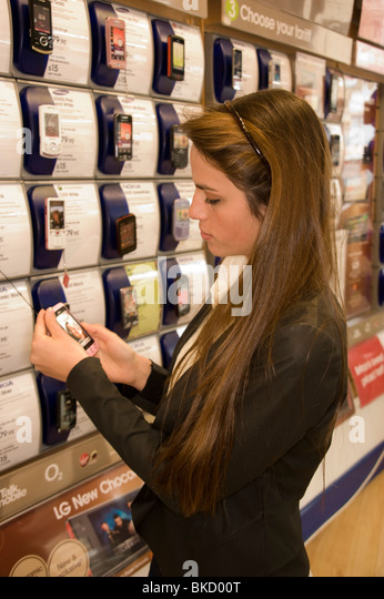 teenage girl in a mobile phone shop looking at phones   Stock Image. Teenage Girls Out Shopping In Stock Photos   Teenage Girls Out