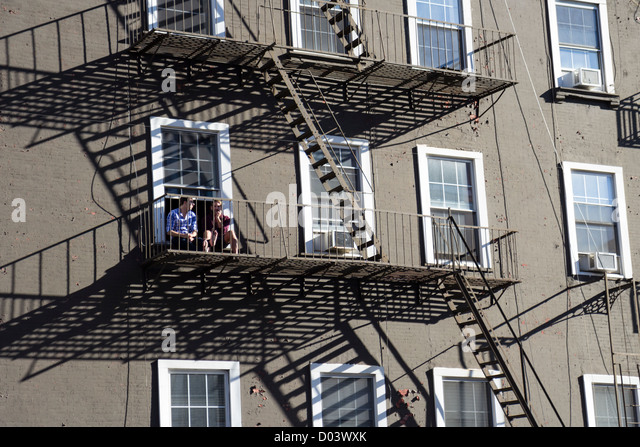 Two Young Men Sitting On The Fire Exit Stairs Of A Building In Manhattan,  New