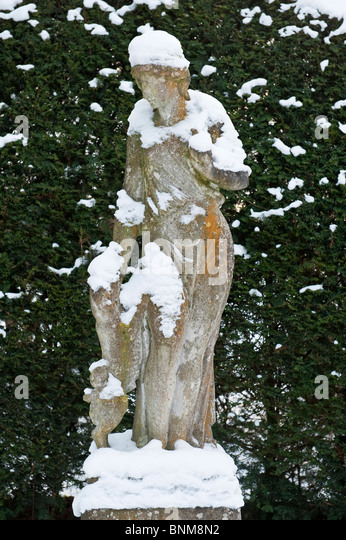 Snow Covered Statue Of A Girl With Her Pet Dog In Front Of A Yew