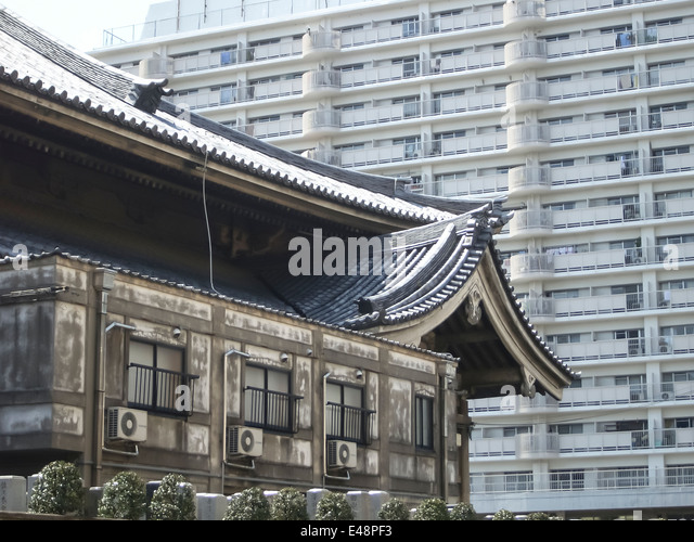 An Old Japanese Building With Traditional Pagoda Roof In Front Of A Modern  Apartment Block In