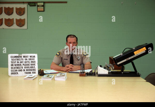 Portrait of American Drivers Licence Officer from 1970 with poster instructing all drivers to be tested with seatbelts - Stock Image