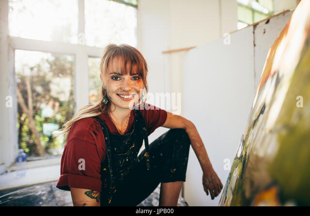 Indoor shot of professional female painter in studio. Woman artist making a painting on canvas in her workshop. - Stock Image