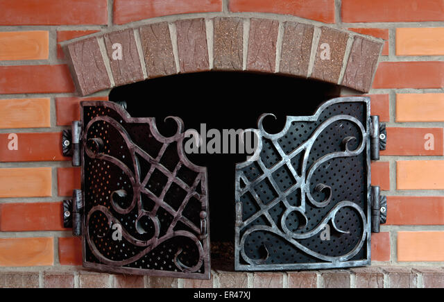 close up of brick fireplace with an iron gate stock image