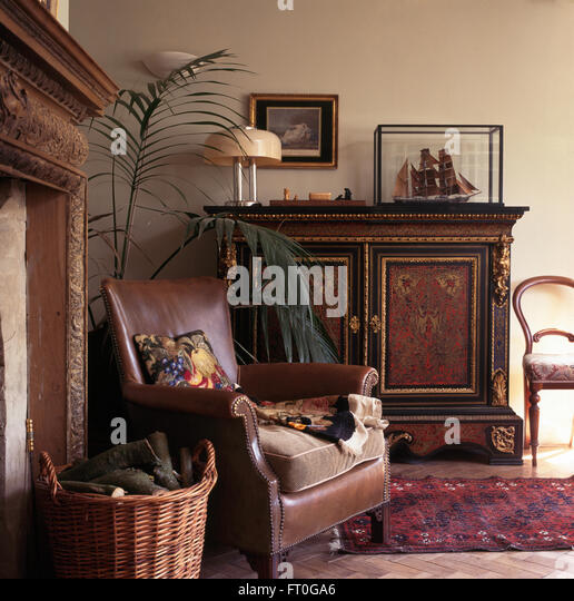 Brown Leather Chair And Ornate Antique Cupboard In Old Fashioned Living Room
