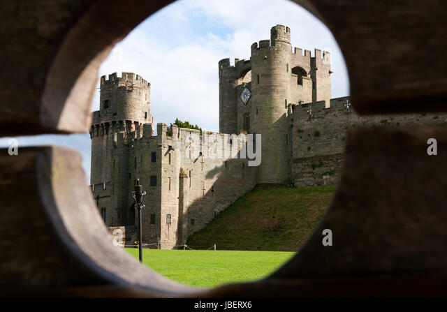 Barbican battlements, front, with the taller Gatehouse / Gate House in the background, seen through wooden stocks. - Stock Image