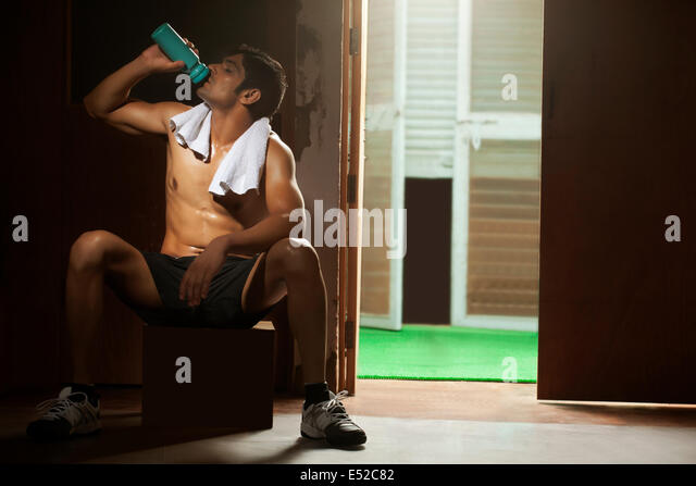 Indian man gym drinking water stock photos indian man gym full length of tired young man drinking water from bottle at gym stock image sciox Choice Image