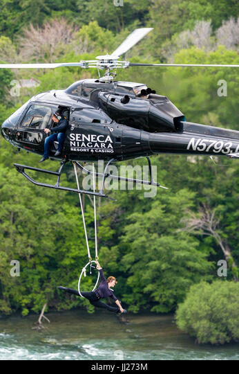 Erendira Wallenda performs stunts under a helicopter while her husband Nik Wallenda watches. - Stock Image