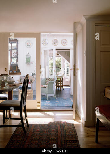 Rug On Wooden Floor In Country Dining Room With Glass Doors To Conservatory Sitting