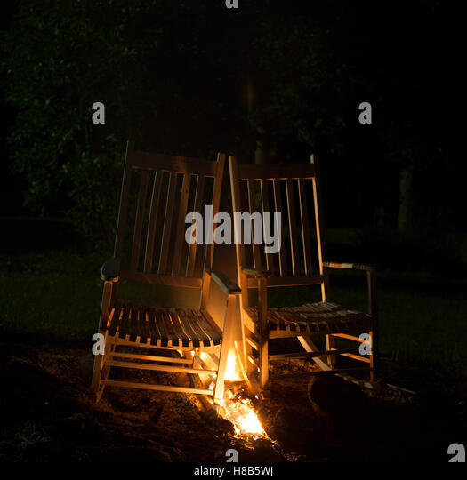 Two Rocking Chairs That Have Fire Between Them   Stock Image