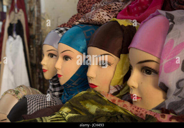 A line of plastic heads modelling headscarves or hijabs sits on a table in a small shop in Fez, Morocco. - Stock Image