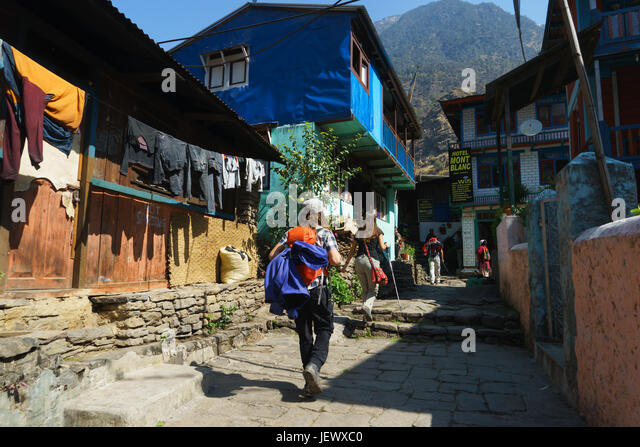 Trekkers going through the village of Jagat, on the Annapurna circuit in Nepal. - Stock Image