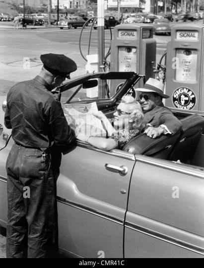 1950s COUPLE WITH MAP IN CAR CONVERTIBLE ASKING DIRECTIONS FROM GAS STATION ATTENDANT
