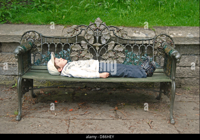 Captivating A Little Boy Lying On An Ornate Garden Bench   Stock Image