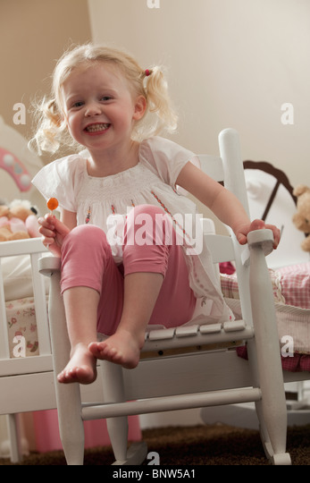 Young girl in rocking chair eating a sucker - Stock Image