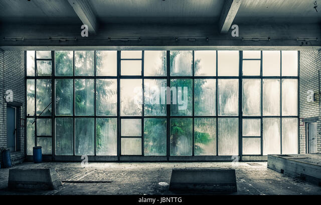 The view from an old, abandoned factory on the inside with nice window light - Stock Image