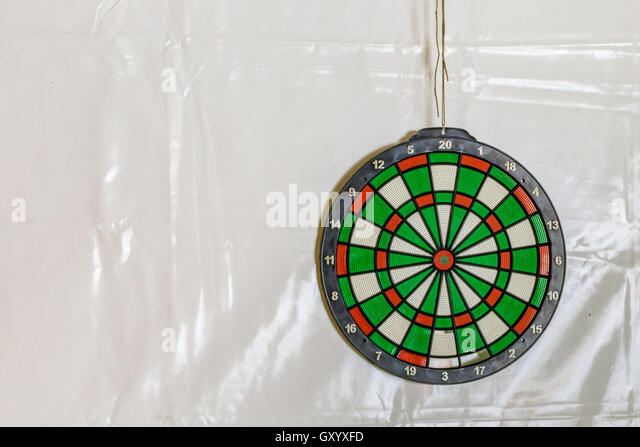 dartboard on the wall covered by plastic tarp