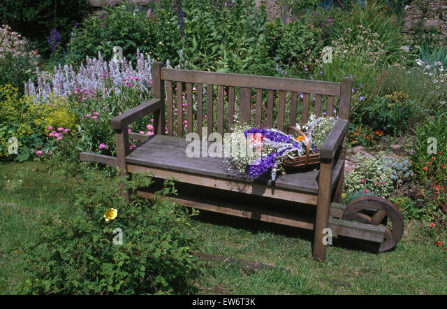 Amazing Wheeled Wooden Bench With A Trug Of Summer Flowers In A Country Garden    Stock Image