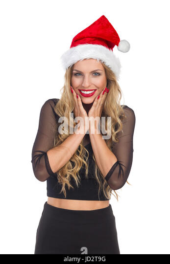 Ecstatic young blond woman in santa's hat and black dress holding head in hands and smiling. Waist up studio - Stock Image