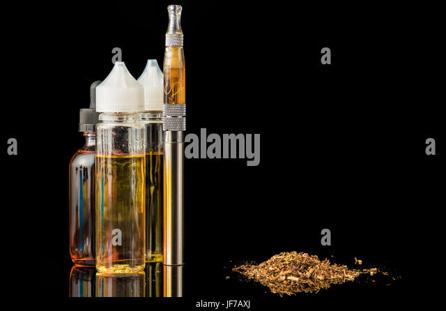 Electronic cigarette with bottles and grinded tobacco leaves - Stock Image