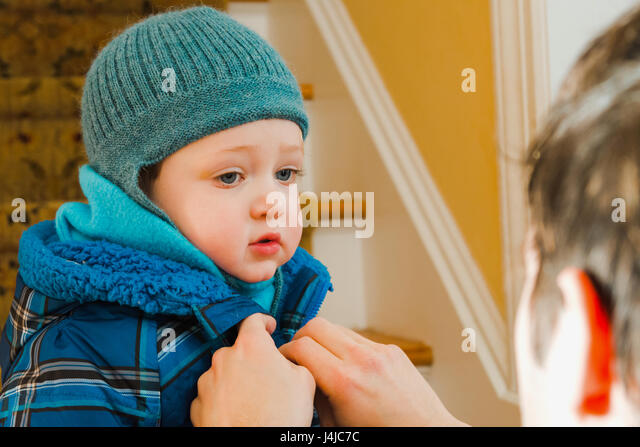 father zipping up son's winter coat - Stock Image