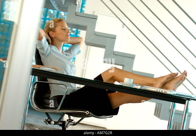 young businesswoman resting in office with legs on desk stock image business nap office relieve