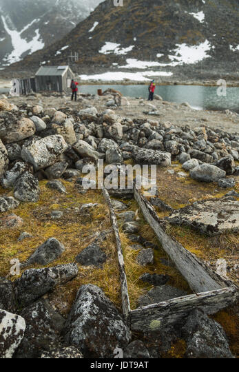 The empty grave of an old whaler lies open to the air near a hut that is still used by hunters in Spitzbergen - Stock Image