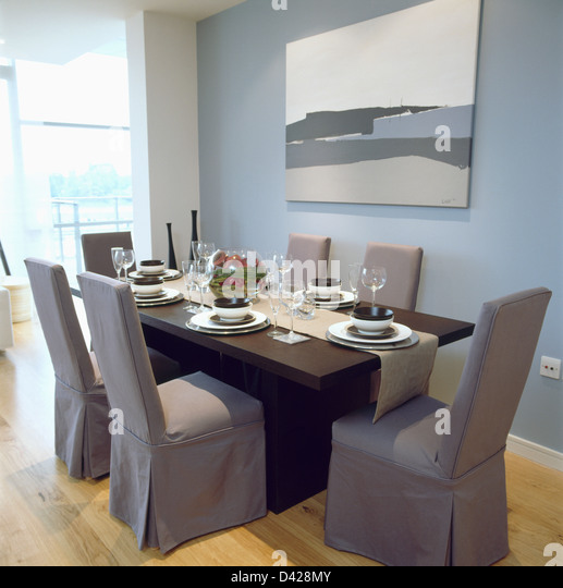 Grey Loose Covers On Chairs At Black Table Set For Lunch With Linen Runner In Modern