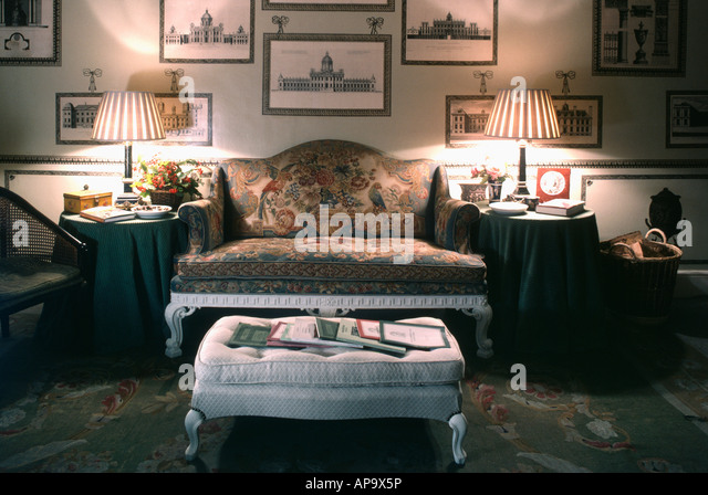 Upholstered stool in front of antique sofa in livingroom room with lighted lamps and pictures on