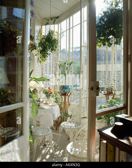 Open Door To Conservatory Diningroom With White Cast Iron Furniture