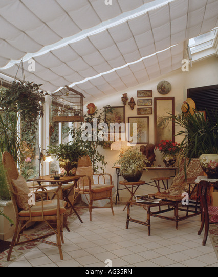 Antique Cane Furniture And Pictures On The Wall In Edwardian Style  Conservatory With White Blinds And