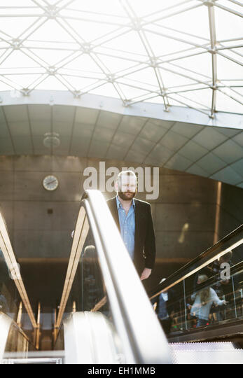 Businessman On Moving Staircase At Subway Station   Stock Image