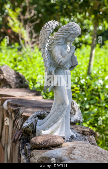 A Small Garden Statue Of A Pensive Or Praying Angel Sits Perched On A Low  Stone
