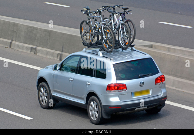 VW Car With Four Bikes Fitted To Roof Rack Driving Along M25 Motorway    Stock Image