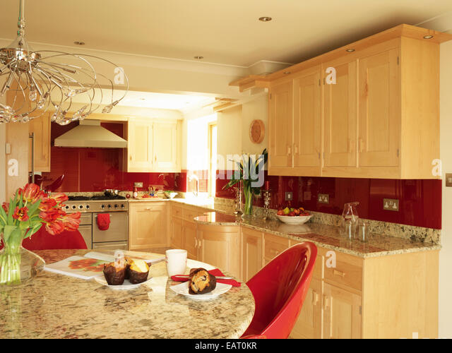 Granite breakfast bar in kitchen stock photos granite for Red fitted kitchen