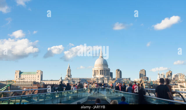 View of the Millennium bridge in London with St Paul cathedral and tourists and commuters walking - Stock Image