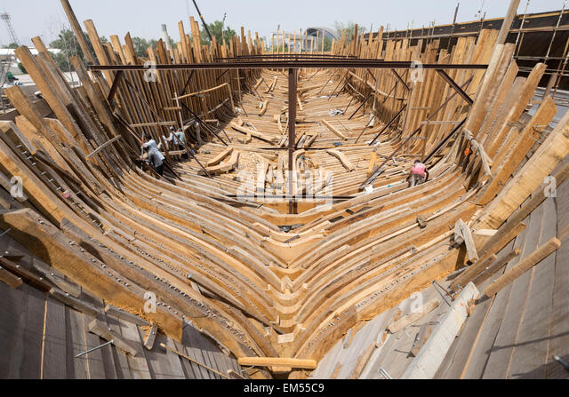 Building A Traditional Wooden Dhow Cargo Ship In Shipyard Beside The Creek River Dubai United