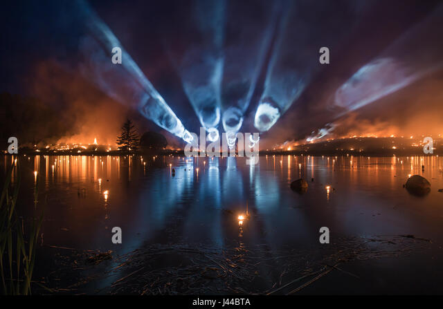 Bright light tubes over a lake with forest fire on background - Stock Image
