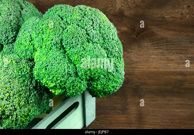 Broccoli heads in crate on rustic texture with copyspace - Stock Image