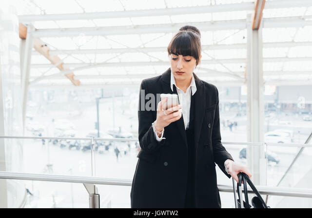 Businesswoman using mobile phone on business trip, Milan, Italy - Stock Image