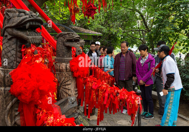 Guilin, China.  Elephant Trunk Hill Park.  Chinese Tourists Regard Red Ribbons Decorating a Tree, Requesting a Wish. - Stock Image
