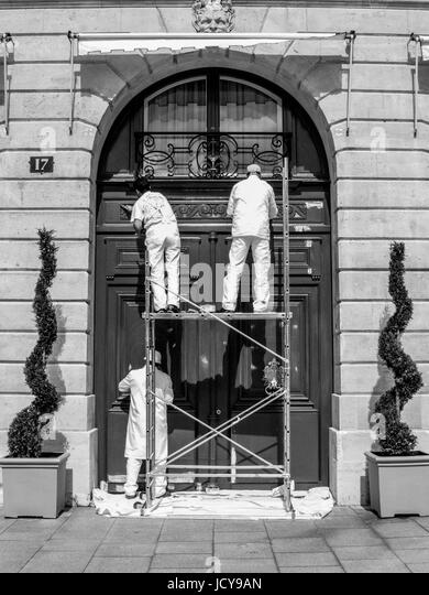 PARIS FRANCE - PAINTERS WORKING ON A LARGE MAIN DOOR IN PLACE VENDOME - STREET PHOTOGRAPHY © Frédéric - Stock Image