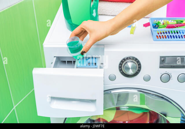 Hand Pours Liquid Powder Into The Washing Machine